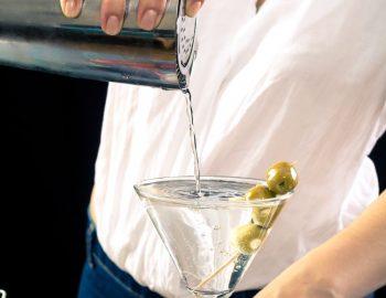 מזיגת משקה צלול לכוס עם שלושה זיתים